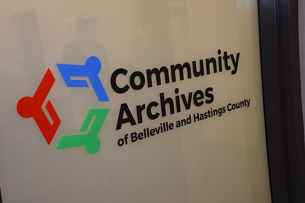 Window with Community Archives logo.