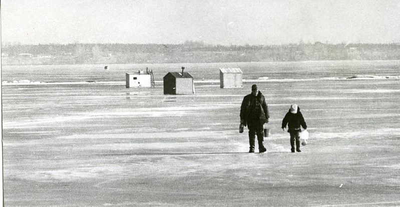 Man and child walking away from ice-fishing huts on frozen Bay of Quinte.