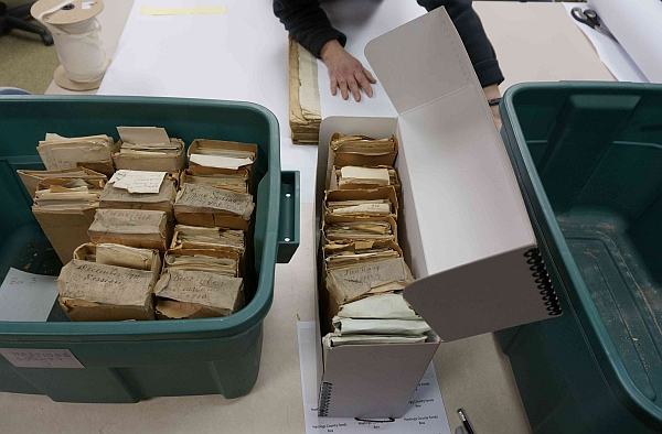 Archival materials being placed in acid-free containers.